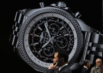 Pedestrian using his mobile phone walks past an advertisement for a luxury brand watch at a shopping district in Tokyo