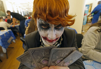 """A man dressed as the """"Joker"""" plays cards during a board games festival in St. Petersburg"""