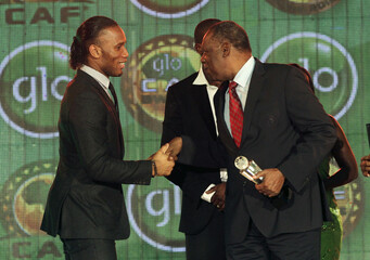 Ivorian soccer player Didier Drogba who plays for Shanghai Shenhua in China shakes hand with Issa Hayatou president of CAF (Confederation Africaine de Football) attends the African soccer player awards ceremony in Accra