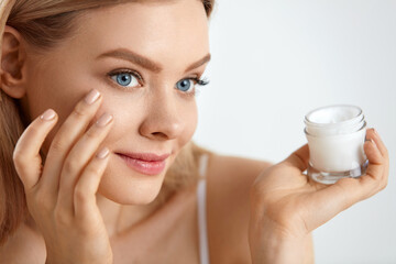 Beauty Woman Face. Girl With Fresh Skin And Cream Bottle In Hand