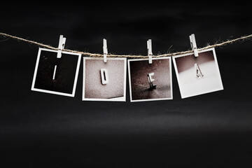 Rows of IDEA letters photo frames hanging with clothespins on dark background