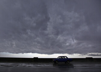 A car is driven along Havana's seafront boulevard 'el Malecon' during a storm