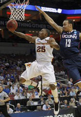 Iowa State University's Tyrus McGee fights to get his shot off under pressure from University of Connecticut's Shabazz Napier in their NCAA basketball game in Louisville
