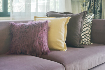 L shape purple sofa with stylish pillows in living room