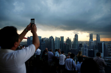 A man takes photos of storm clouds gathering over the skyline of Singapore's central business district