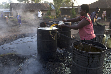 """Woman pours water to cool down an overheated distilling drum as she brews crude gin, known locally as """"Waragi, at Musoto village on the outskirts of Mbale town"""