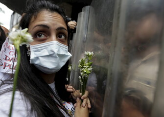 A supporter of jailed Venezuelan opposition leader Leopoldo Lopez, wearing a face mask to represent their hunger strike in solidarity with Lopez, holds flowers in front of police officers outside the CNE offices in Caracas