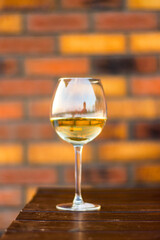 Glass with white wine on the desk, brick background
