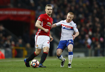 Wigan Athletic's David Perkins in action with Manchester United's Luke Shaw