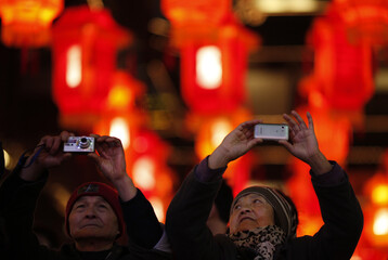 A couple takes pictures of red lantern decorations ahead of the Chinese Lunar New Year in Shanghai