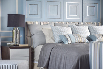 Striped an cross pattern pillows in light blue tone on classic gray bedding in classic light blue bedroom
