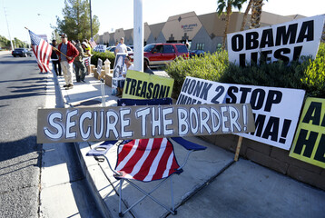 Protesters gather signs across the street from Del Sol High School where U.S. President Obama is scheduled to deliver remarks on his use of executive authority to relax U.S. immigration policy in Las Vegas, Nevada