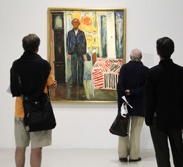 """Guests look at the painting """"Self portrait, between the clock and the bed"""" by Norwegian artist Edvard Munch is seen at the Centre Pompidou modern art museum in Paris"""