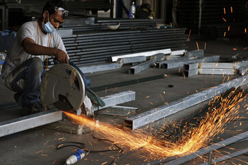 A worker cuts steel at a factory in the industrial zone of Jurong in western Singapore