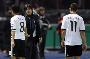 Germany's coach Loew looks at Oezil and Klose after the Euro 2012 qualifying soccer match against Turkey at the Olympic stadium in Berlin