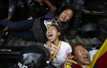 Nepalese police personnel detain Tibetan activists during their protest near the Chinese Embassy Consular office in Kathmandu