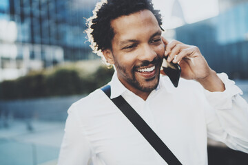 Closeup portrait of smiling American African man using smartphone to call friends at sunny street.Concept of happy young handsome people enjoying gadgets outdoors.Blurred background.