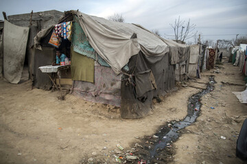 A teenager stands at his father's shop at a slum on the outskirts of Islamabad