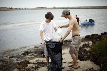 Brothers Jonas Powers and Dawson McCall remove debris from the beach in a coast-wide cleanup effort at Bay St. Louis