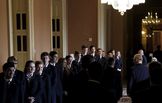 Senate pages line a hallway to greet Britain's Prince Charles as he walks to meet McConnell at the U.S. Capitol in Washington,