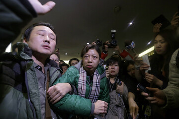 A woman, whose husband is a passenger of Malaysia Airlines flight MH370, attempts to leave a hotel after complaining about Malaysia Airlines, in Beijing