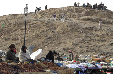 Muslims climb and stand atop an area of Mount Uhud, north of the holy city of Madinah