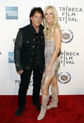 "Neal Schon of the band Journey arrives with Michaele Salahi for the premiere of ""Don't Stop Believin': Everyman's Journey"" during the 2012 Tribeca Film Festival in New York"