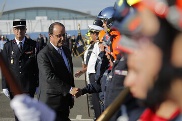President of the firefighters national federation Eric Faure and French President Francois Hollande review firemen during the national firemen's congress in Tours