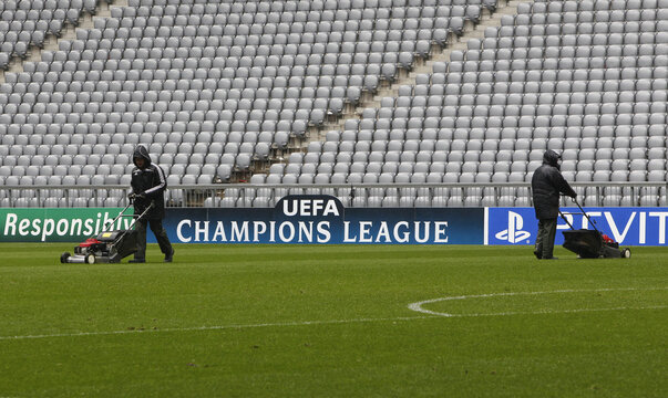 Workers mow the lawn in Munich's Allianz Arena