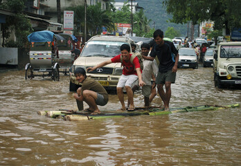 People laugh as they play on a raft made from banana tree trunks after heavy rains flooded the northeastern Indian city of Guwahati
