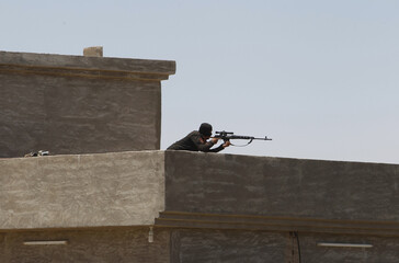A member of the Iraqi security forces aims his rifle as he takes up position during an intensive security deployment west of Baghdad