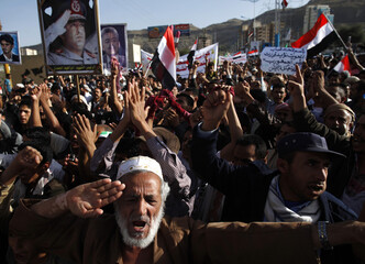 Pro-democracy protesters shout slogans hailing a military shake-up by Yemen's President Hadi during a demonstration outside his house in Sanaa