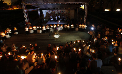 People hold candles as they watch a performance during Earth Hour in Sao Paulo