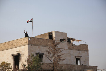 Forces loyal to Syria's President Bashar al-Assad gesture atop a building in Aleppo countryside