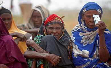 Internally displaced people who fled flooding of the overflowed Shabelle river wait to receive relief assistance near Baledweyne town central Somalia