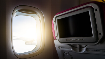 Window with sunlight and Private monitor on airplane seat to entertainment service for passenger in travel concept..