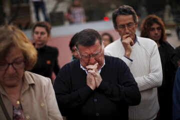 People observe a minute of silence for over 700 migrants who died on Sunday after their boat capsized in the Mediterranean, in Malaga