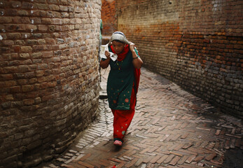 A woman carrying goods walks at a small alley of the ancient city of Bhaktapur