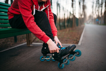 Roller skater sitting on bench and lace up skates