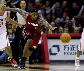 Miami Heat forward James chases a loose ball with Houston Rockets guard Battier in the background during their NBA game in Houston