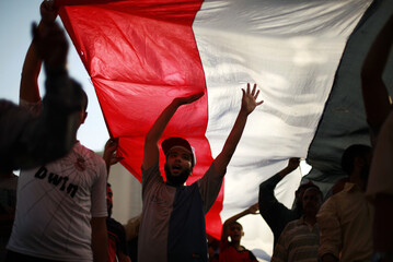 Supporters of the Muslim Brotherhood of Egypt march under a giant Egyptian national flag during a protest at Tahrir Square in Cairo