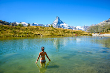 Girl swimming in lake Leisee with view to the Matterhorn mountain in beautiful landscape of the Alps at Zermatt, Switzerland