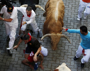 Runners fall in the way of fighting bulls at the entrance to the bullring during the seventh running of the bulls of the San Fermin festival in Pamplona
