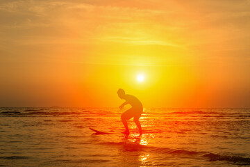 Vacation Concept ; Happy surfer playing with surfboards on the beach, at sunset,Phuket,Thailand