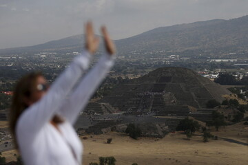 A view of the Pyramid of the Moon is seen in the background while a woman raises her arms towards the sun to welcome the spring equinox in the pre-hispanic city of Teotihuacan on the outskirts of Mexico City