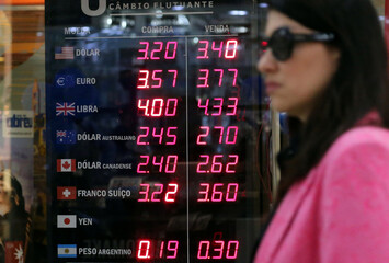 Woman walks near a board showing the Brazilian Real-U.S. dollar and several other foreign currencies exchange rates in Rio de Janeiro
