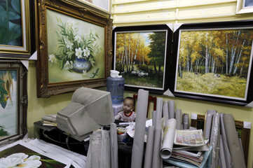 A two-year-old boy, the son of a vendor, watches cartoons at a gallery at Dafen Oil Painting Village, in Shenzhen