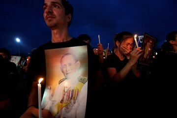 Mourners hold up pictures of Thailand's late King Bhumibol Adulyadej and candle lights during a vigil to mark his birthday outside the Grand Palace in Bangkok