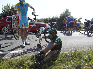 Europcar rider Vincent Jerome of France is assisted after a crash in the first stage of the Tour de France 2011cycling race