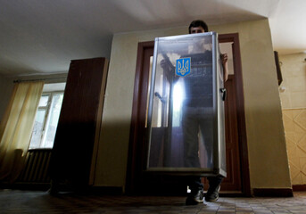 Election commission worker carries a ballot box at a polling station for Sunday's referendum in the eastern Ukrainian city of Lugansk